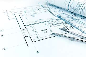 rolled blueprints, ruler and drawing compass on graphical architectural project of apartment