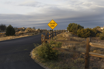 a dead end sign lit by the rising sun