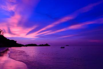 Landschapsmening van zonsondergang op het strand met dramatische lucht en zonlicht.