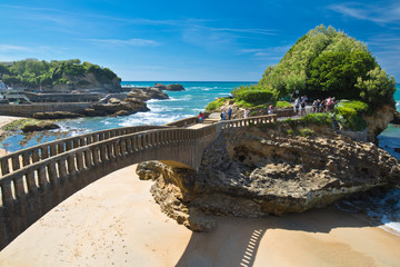 people walking on footbridge leading to cliff island over sandy beach in touristic destination surf spot with turquoise ocean and waves in biarritz in blue sky, basque country, france