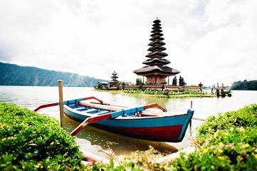 Pura Ulun Danu Bratan. Ancient Balinese temple located on the water, Bratan Lake, Bali, Indonesia. Traditional Indonesian fishing boat on the foreground.