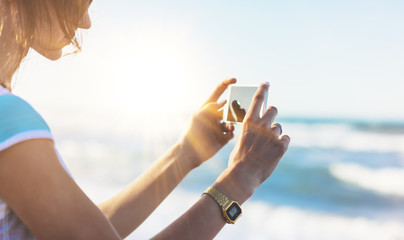 Hipster girl photograph on smart phone gadget in sand coastline, mock up of blank screen. Traveler using in female hand mobile on background seascape horizon. Tourist look on blue sun ocean, lifestyle