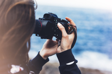 Tourist traveler photographer girl taking pictures of seascape on modern photo camera on background blue ocean view mockup sun flare, hipster female hands shoots video, nature holiday concept