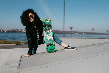 Pretty teen girl spending time in the park near the water with his skate