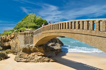 people walking on stone footbridge in scenic seascape on atlantic coastline in blue sky in basque country, biarritz, france