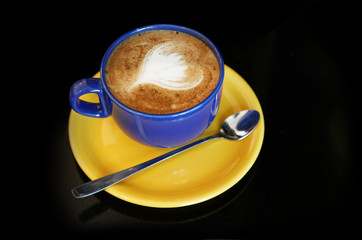 Cappuccino in a blue cup on a yellow saucer