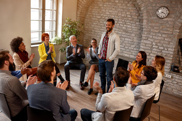 discussion business group- coworkers applauding man in group.