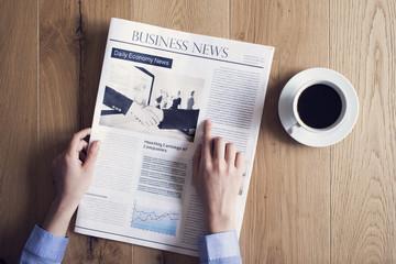 Reading newspaper on desk