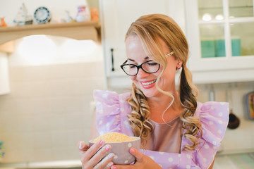 beautiful young housewife in the kitchen in a pink apron