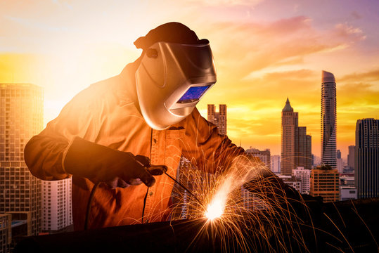 Industrial worker welding steel of construction structure for infrastructure architecture building project.