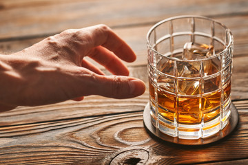 Man's hand reaching to glass of whiskey with ice cubes. Alcoholism concept.