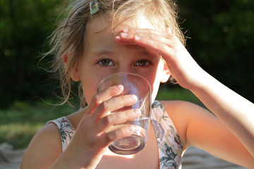 Portrait blondes Mädchen trinkt Wasser aus Glas