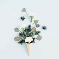 Waffle cone with white carnation and eucalyptus bouquet on pale pastel blue background. Flat lay, top view