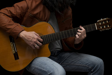 Long hair male guitarist playing with acoustic guitar in leather jacket on the stage.