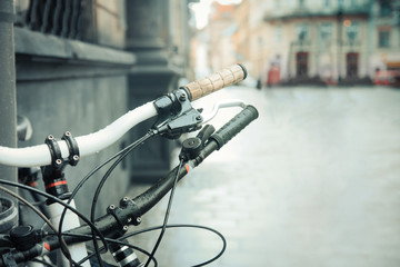 Bicycle close-up on a city street. Beautiful vintage urban background.
