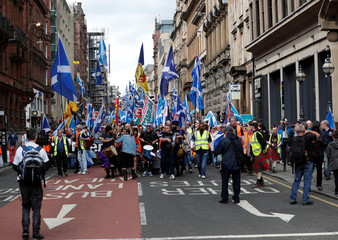 Demonstrators carry Scottish flags at a march in support of Scottish independence in Glasgow