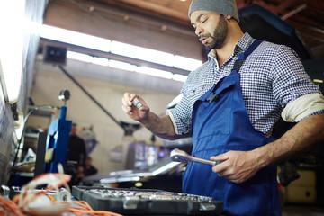 Young mechanic in uniform working in garage