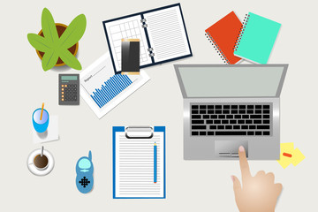 Top view of home office desk with supplies, coffee cup and electronic baby monitor. Female hand is touching touchpad of laptop.