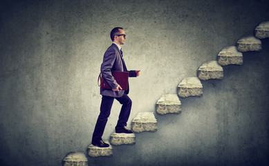 Businessman with briefcase stepping up a stairway career ladder