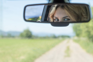The beautiful eyes of the young driver woman are reflected in the rearview mirror. Blurred road and landscape is in the background.