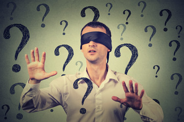 blindfolded man stretching his arms out walking through many question marks