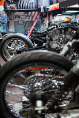 Row of disassembled motorcycles set for tuning up and customizing in mechanics workshop