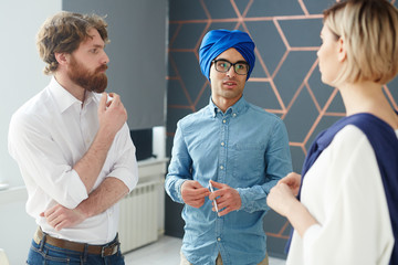 Businessman in turban explaining his idea to colleagues