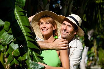 portrait d'un beau couple souriant dans des feuilles de bananier