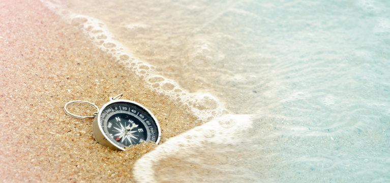 Vintage style of tourist compass on the sand beach