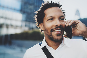 Closeup portrait of happy American African man using smartphone to call his friends at sunny city.Concept of happy young handsome people enjoying gadgets outdoor.Blurred background.