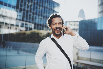 Portrait of happy American African man using smartphone to call his friends at sunny city.Concept of happy young handsome people enjoying gadgets outdoor.Blurred background.