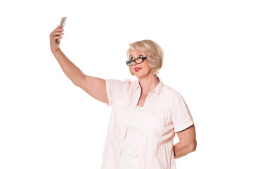 elderly woman with glasses makes selfie over a white background, space for text