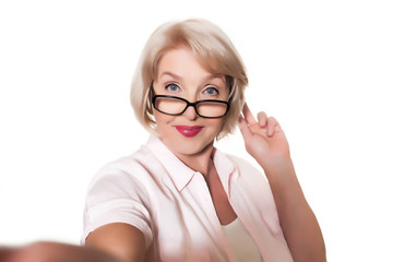 Beautiful elderly woman with glasses makes selfie over a white background