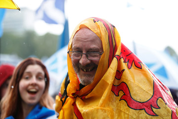 Demonstrator wraps a flag around himself at a march in support of Scottish independence in Glasgow