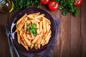 Penne pasta with tomato sauce on dark wooden background top view. Italian cuisine.