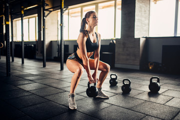Woman doing exercise with weight in fitness club