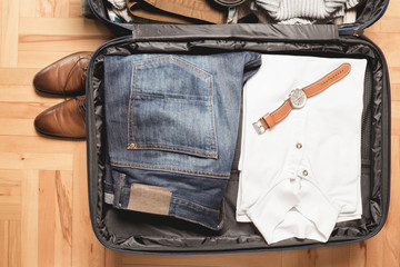 Open traveler's bag with men clothing, accessories, watch and belt. Travel and vacations concept.