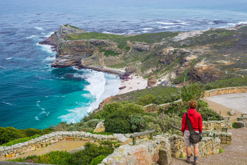 Tourist hiking at Cape Point, looking at view of Cape of Good Hope and Dias Beach, scenic travel destination in South Africa. Table Mountain National Park, Cape Peninsula.