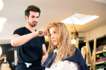 Attractive hairdresser making hair style