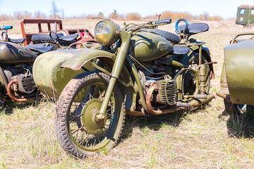 Russian vintage rusty motorcircle at the field in sunny day