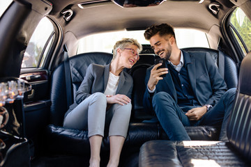 Business woman and business man having laugh in limo