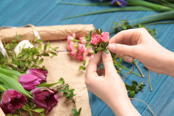 Female florist making floral composition on wooden table