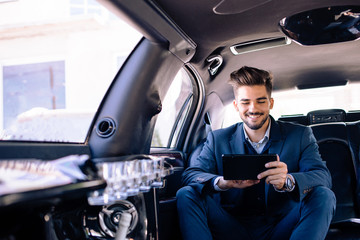 Businessman is looking at tablet and smiling in limo