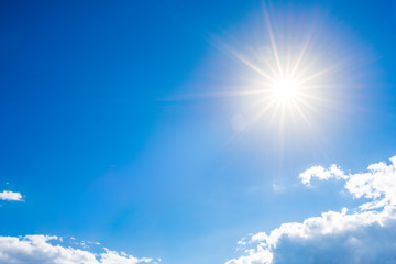 Sunny background, blue sky with clouds and bright sun