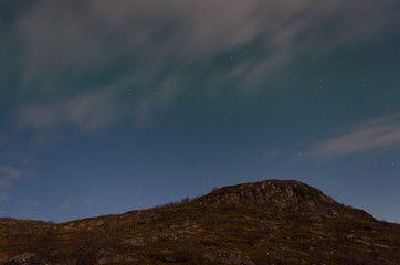 The Aurora in the sky above the hills in the moonlight.