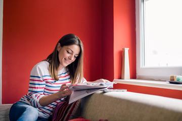 Girl reading magazine beside window