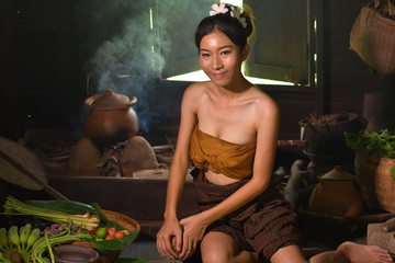An Asian girl cooking in a traditional Thai country kitchen