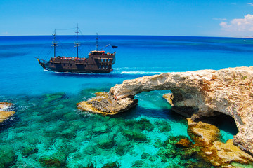 Pirate ship sailing near famous rock arch on Cavo Greko peninsula, Cyprus island
