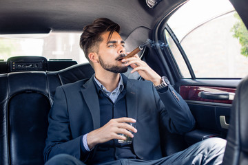 Young business man enjoying cigar and drink in limo