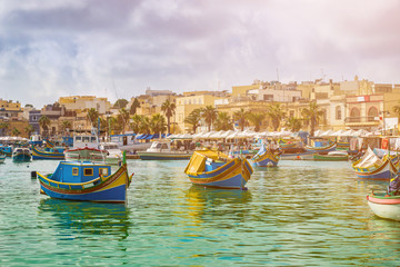 Marsaxlokk, Malta - Traditional colorful maltese Luzzu fisherboats at the old village of Marsaxlokk with turquoise sea water and palm trees on a summer day